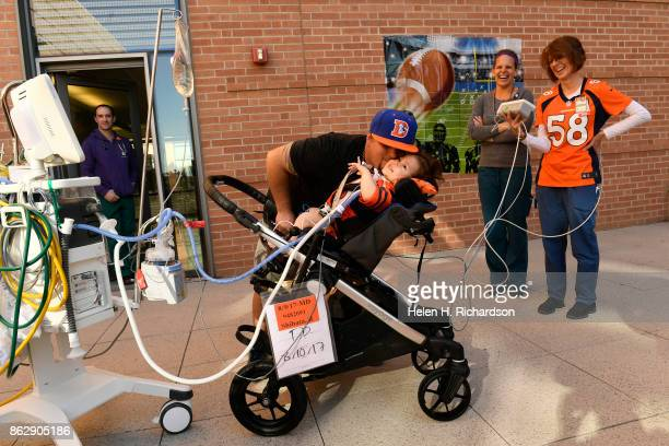 AURORA CO OCTOBER 18 Casey Christensen kisses his son Ryker Christensen who giggles and squints in the daylight in a courtyard at Children's Hospital...