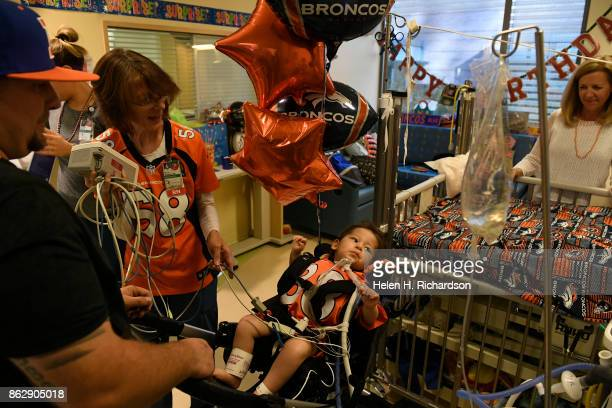 AURORA CO OCTOBER 18 Casey Christensen left and ICU nurse Beth Widner second from left load Casey's son Ryker Christensen into a chair to be able to...