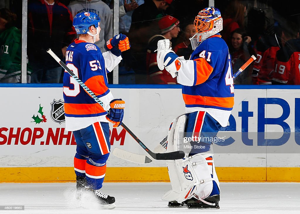 Casey Cizikas and Jaroslav Halak of the New York Islanders celebrate after defeating the New Jersey Devils in a shootout at Nassau Veterans Memorial...