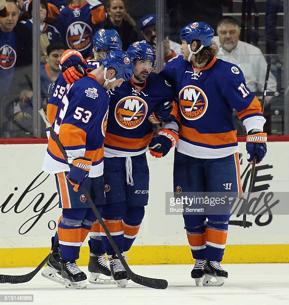 Casey Cizikas and Matt Martin of the New York Islanders escourt Cal Clutterbuck of the New York Islanders off the ice following a second period...