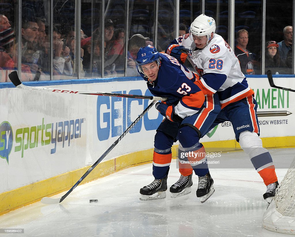Casey Cizikas #53 of Team Blue is checked by Johan Sundstrom #28 of Team White during a scrimmage match between players of the New York Islanders and Bridgeport Sound Tigers on January 16, 2013 at Nassau Veterans Memorial Coliseum in Uniondale, New York.