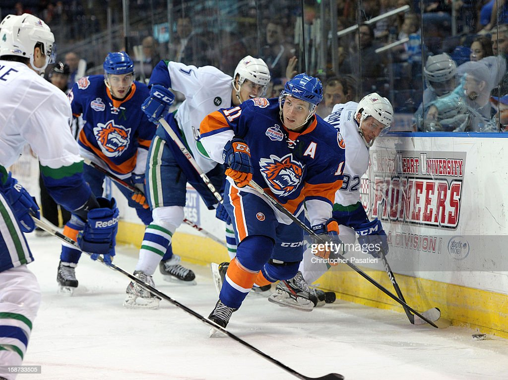 Casey Cizikas #11 of the Bridgeport Sound Tigers reaches for the puck against Christian Thomas #92 of the Connecticut Whale during an American Hockey League game on December 26, 2012 at the Webster Bank Arena at Harbor Yard in Bridgeport, Connecticut.