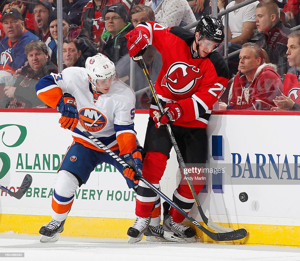 Casey Cizikas #53 of the New York Islanders and Ryan Carter #20 of the New Jersey Devils battle along the boards for a loose puck during the game at the Prudential Center on January 31, 2013 in Newark, New Jersey.