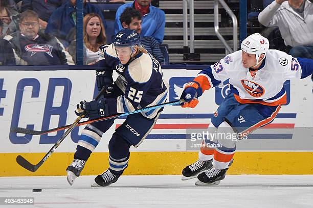 Casey Cizikas of the New York Islanders attempts to lift the stick of William Karlsson of the Columbus Blue Jackets during the first period in NHL...