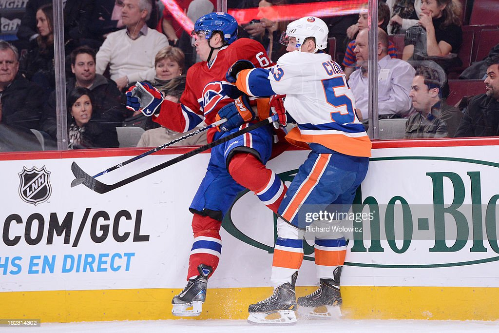 Casey Cizikas #53 of the New York Islanders body-checks Raphael Diaz #61 of the Montreal Canadiens during the NHL game at the Bell Centre on February 21, 2013 in Montreal, Quebec, Canada.