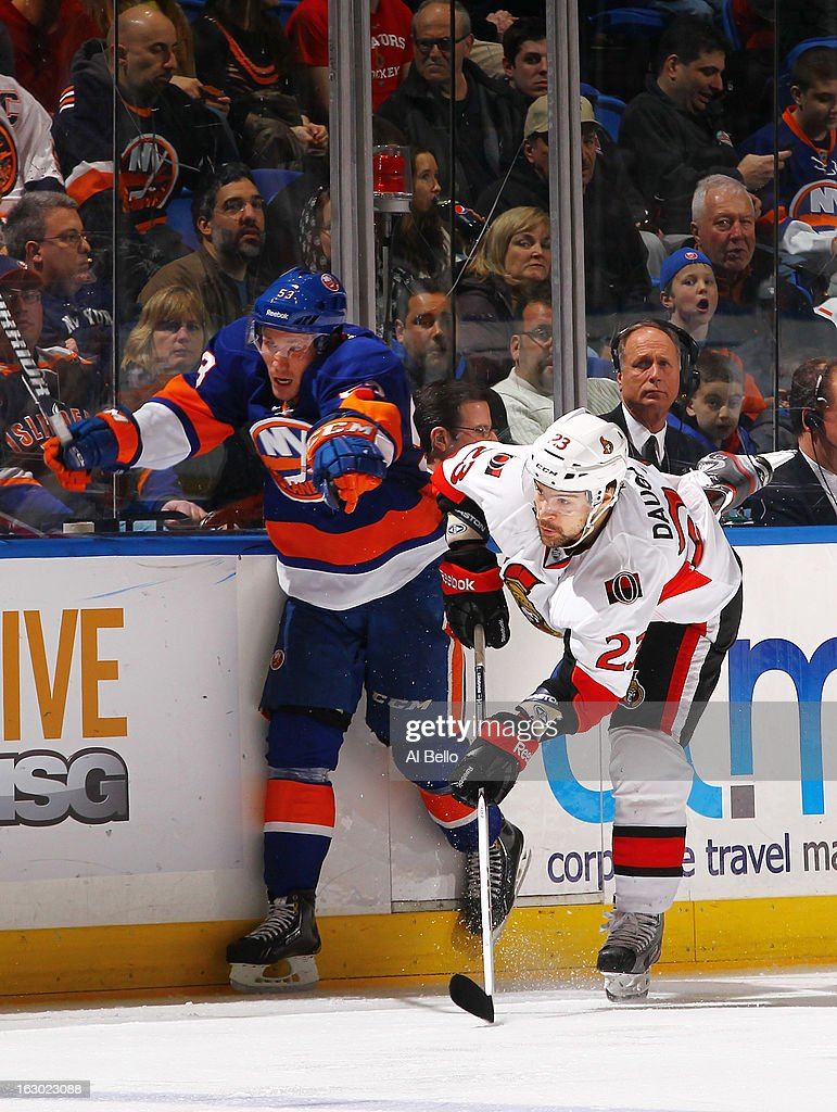 Casey Cizikas #53 of the New York Islanders is checked by Kaspars Daugavins #23 of the Ottawa Senators during their game at Nassau Veterans Memorial Coliseum on March 3, 2013 in Uniondale, New York.