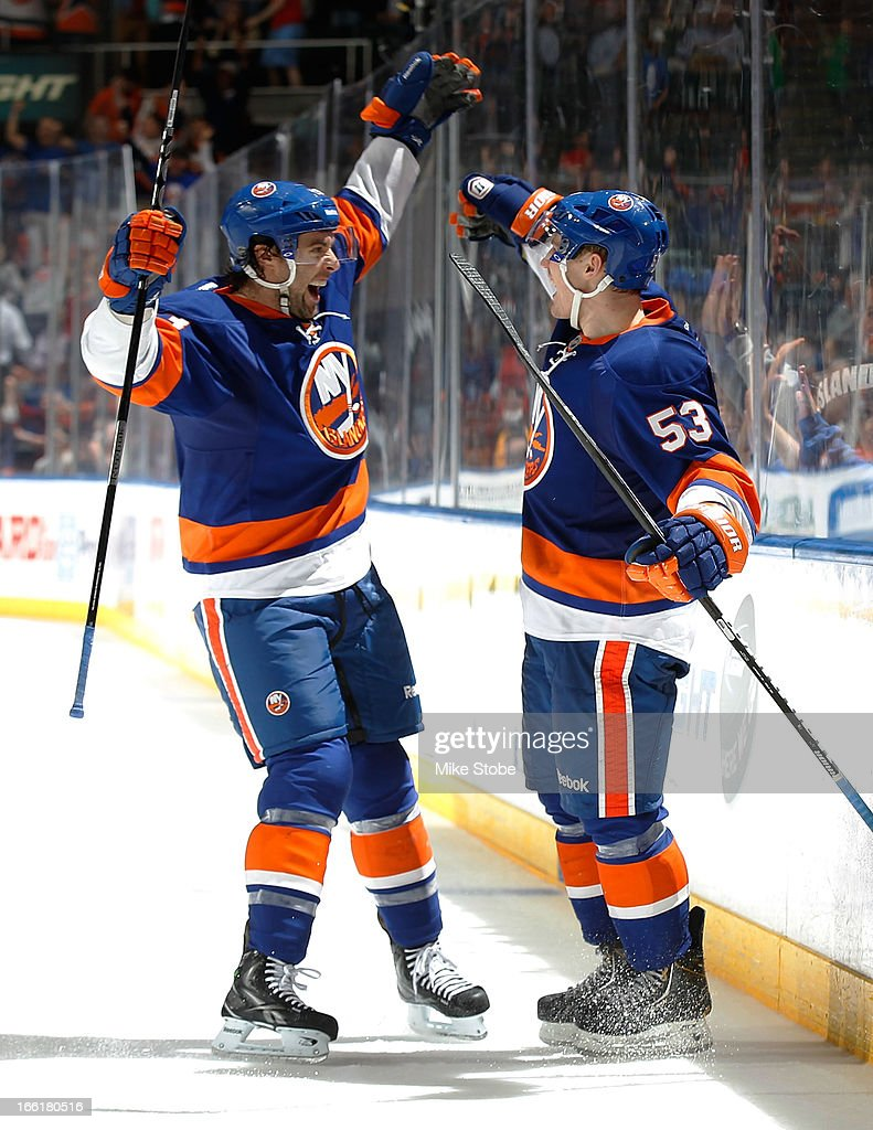 Casey Cizikas #53 of the New York Islanders is congratulated by teammate Colin McDonald #13 on his third period goal during the game against the Philadelphia Flyers at Nassau Veterans Memorial Coliseum on April 9, 2013 in Uniondale, New York. The Islanders defeated the Flyers 4-1.