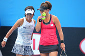Casey Dellacqua of Australia and Kimiko DateKrumm of Japan talk tactics in their first round doubles match against Shuai Peng of China and YiFan Xu...