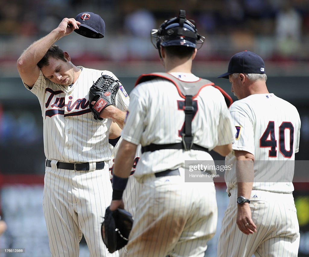 Casey Fien #50 of the Minnesota Twins reacts as <a gi-track='captionPersonalityLinkClicked' href=/galleries/search?phrase=Joe+Mauer&family=editorial&specificpeople=214614 ng-click='$event.stopPropagation()'>Joe Mauer</a> #7 and Rick Anderson #40 visit the mound during the seventh inning of the game against the Cleveland Indians on August 14, 2013 at Target Field in Minneapolis, Minnesota.