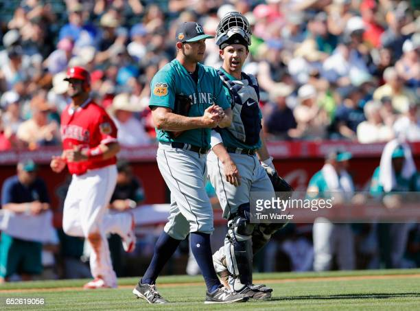 Casey Fien of the Seattle Mariners talks with Tuffy Gosewisch after giving up a home run in the third inning during a spring training game against...