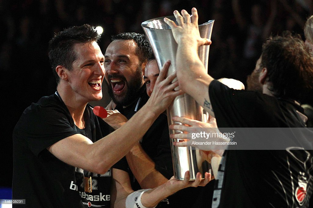 Casey Jacobsen (L) of Bamberg presents the Champions Trophy to his team mates after winning game 3 of the Beko BBL finals between Brose Baskets and ratiopharm Ulm at Stechert Arena on June 10, 2012 in Bamberg, Germany.