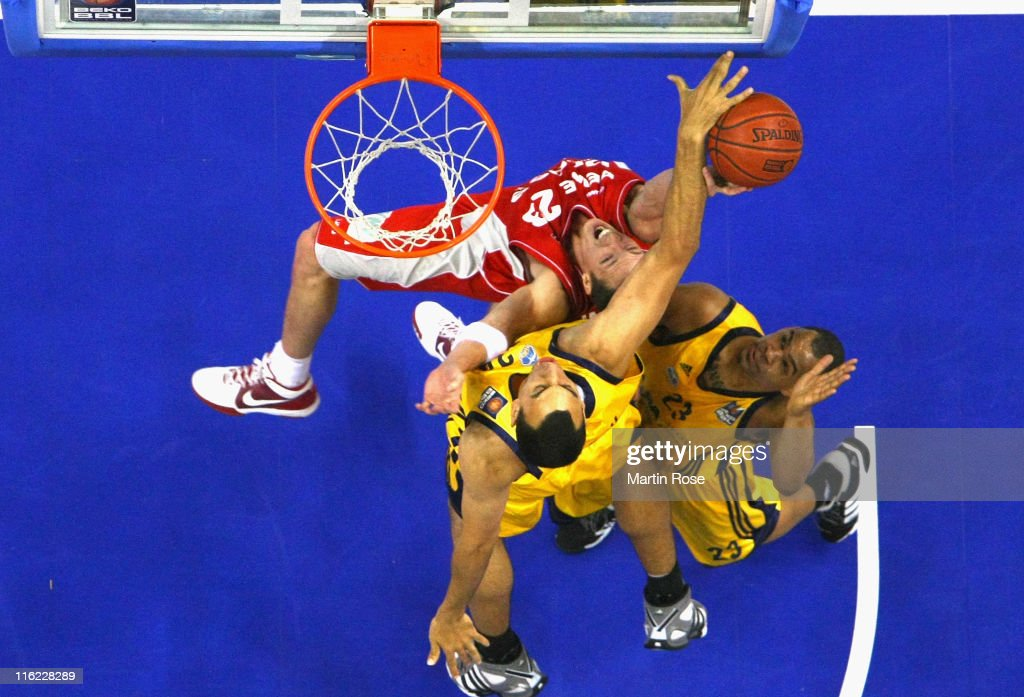 Casey Jacobsen (#23) of Bamberg tries to score over Lucca Staiger (L) and Immanuel McElroy (R) of Berlin during the Beko BBL Playoffs Final game four between Alba Berlin and Brose Baskets Bamberg at O2 World on June 14, 2011 in Berlin, Germany.