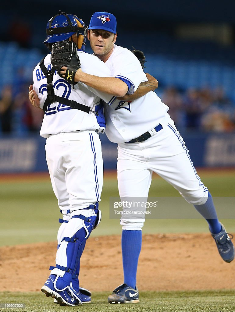 Casey Janssen #44 of the Toronto Blue Jays celebrates their victory with Henry Blanco #22 during MLB game action against the Chicago White Sox on April 18, 2013 at Rogers Centre in Toronto, Ontario, Canada.