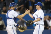 Casey Janssen of the Toronto Blue Jays celebrates with Erik Kratz after a victory against the Cleveland Indians on May 15 2014 at Rogers Centre in...