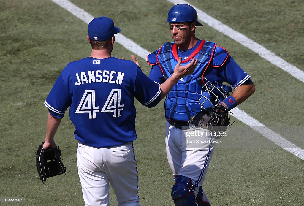 <a gi-track='captionPersonalityLinkClicked' href=/galleries/search?phrase=Casey+Janssen&family=editorial&specificpeople=598479 ng-click='$event.stopPropagation()'>Casey Janssen</a> #44 of the Toronto Blue Jays celebrates with <a gi-track='captionPersonalityLinkClicked' href=/galleries/search?phrase=J.P.+Arencibia&family=editorial&specificpeople=4959430 ng-click='$event.stopPropagation()'>J.P. Arencibia</a> #9 after defeating the Cleveland Indians in MLB game action on July 14, 2012 at Rogers Centre in Toronto, Ontario, Canada.