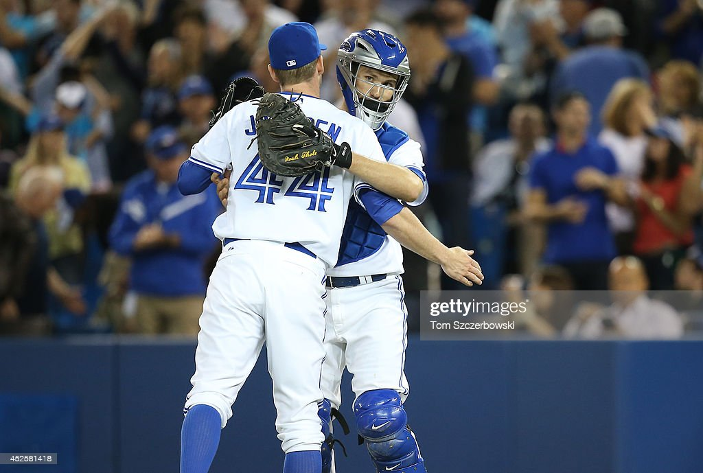 <a gi-track='captionPersonalityLinkClicked' href=/galleries/search?phrase=Casey+Janssen&family=editorial&specificpeople=598479 ng-click='$event.stopPropagation()'>Casey Janssen</a> #44 of the Toronto Blue Jays is congratulated by <a gi-track='captionPersonalityLinkClicked' href=/galleries/search?phrase=Josh+Thole&family=editorial&specificpeople=5741573 ng-click='$event.stopPropagation()'>Josh Thole</a> #22 after defeating the Boston Red Sox in MLB game action on July 23, 2014 at Rogers Centre in Toronto, Ontario, Canada.