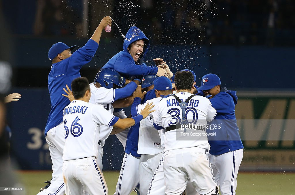 <a gi-track='captionPersonalityLinkClicked' href=/galleries/search?phrase=Casey+Janssen&family=editorial&specificpeople=598479 ng-click='$event.stopPropagation()'>Casey Janssen</a> #44 of the Toronto Blue Jays jumps on a pile of players, including <a gi-track='captionPersonalityLinkClicked' href=/galleries/search?phrase=Melky+Cabrera&family=editorial&specificpeople=453444 ng-click='$event.stopPropagation()'>Melky Cabrera</a> #53, whose sacrifice bunt resulted in a throwing error resulting in the winning run in the ninth inning during MLB game action against the New York Yankees on June 24, 2014 at Rogers Centre in Toronto, Ontario, Canada.