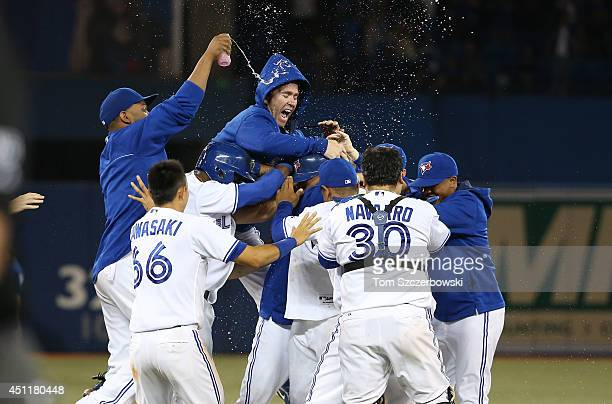 Casey Janssen of the Toronto Blue Jays jumps on a pile of players including Melky Cabrera whose sacrifice bunt resulted in a throwing error resulting...