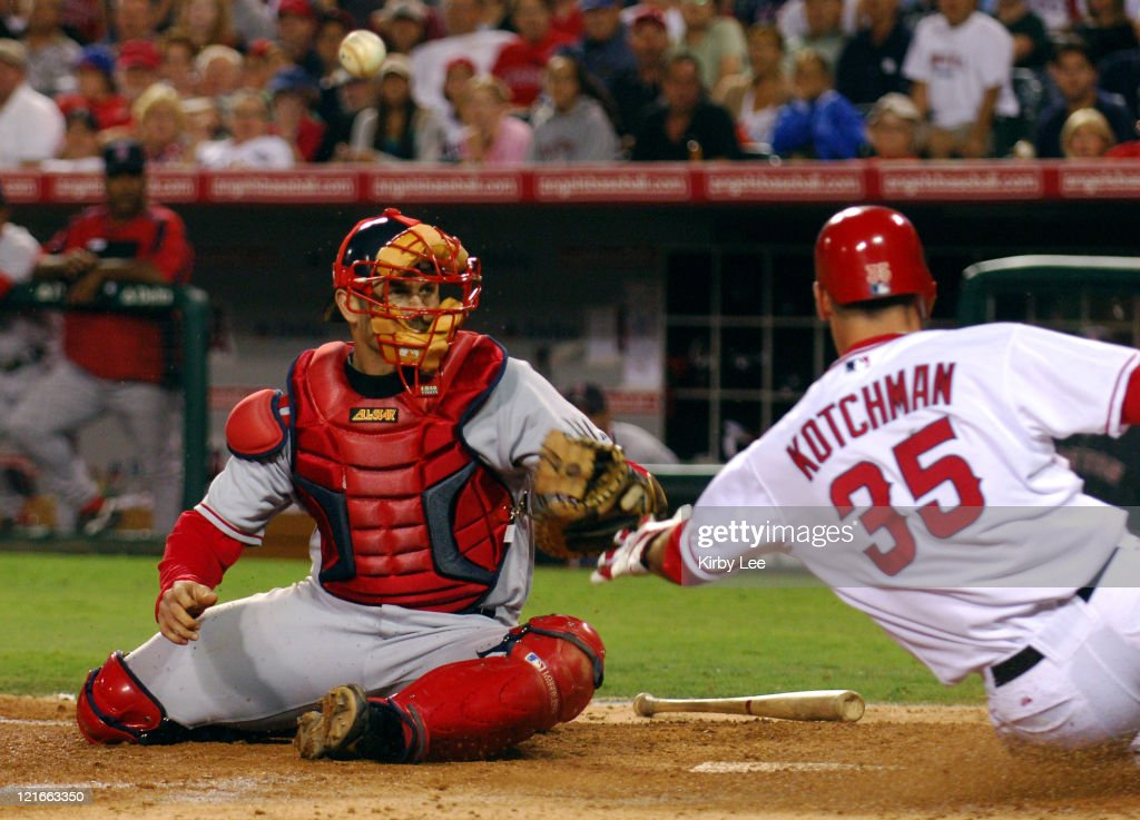 Casey Kotchman of the Los Angeles Angels of Anaheim slides safety into home plate after a bobbled throw to Boston Red Sox catcher <a gi-track='captionPersonalityLinkClicked' href=/galleries/search?phrase=Jason+Varitek&family=editorial&specificpeople=171480 ng-click='$event.stopPropagation()'>Jason Varitek</a> in the fifth inning of 4-3 loss in 10 innings to the Boston Red Sox at Angel Stadium in Anaheim, Calif. on Friday, August 19, 2005.