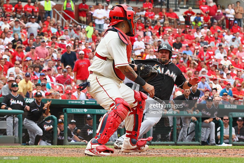 <a gi-track='captionPersonalityLinkClicked' href=/galleries/search?phrase=Casey+McGehee&family=editorial&specificpeople=796577 ng-click='$event.stopPropagation()'>Casey McGehee</a> #9 of the Miami Marlins scores the game-winning run against <a gi-track='captionPersonalityLinkClicked' href=/galleries/search?phrase=Yadier+Molina&family=editorial&specificpeople=172002 ng-click='$event.stopPropagation()'>Yadier Molina</a> #4 of the St. Louis Cardinals at Busch Stadium on July 5, 2014 in St. Louis, Missouri. The Marlins beat the Cardinal 6-5.