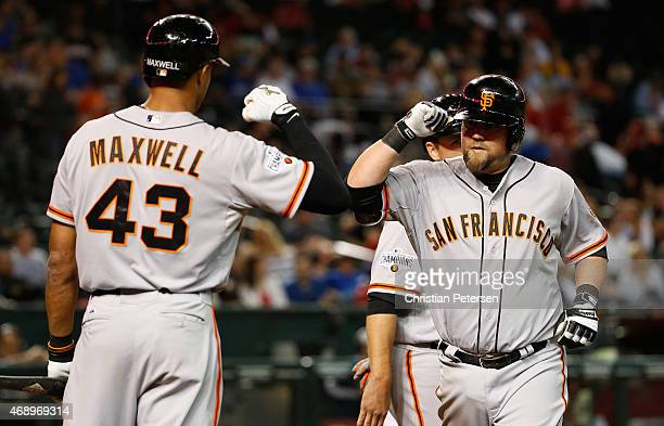 Casey McGehee of the San Francisco Giants highfives Justin Maxwell at home plate after McGehee hit a tworun home run against the Arizona Diamondbacks...