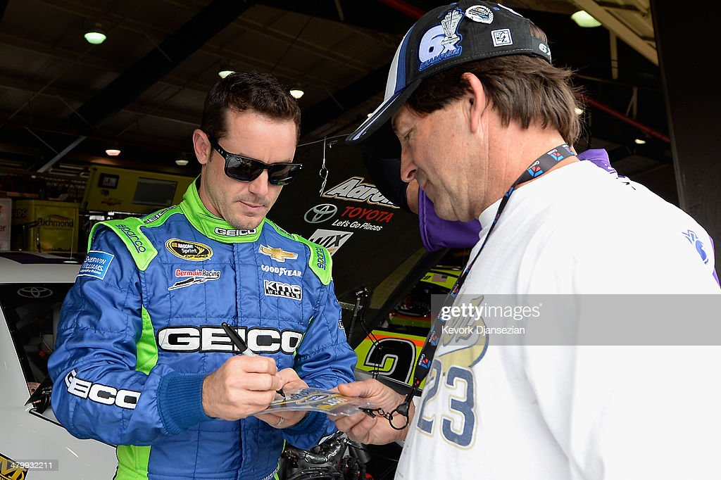Casey Mears, driver of the #13 GEICO Chevrolet, signs an autograph for a fan during practice for the NASCAR Sprint Cup Series Auto Club 400 at Auto Club Speedway on March 21, 2014 in Fontana, California.