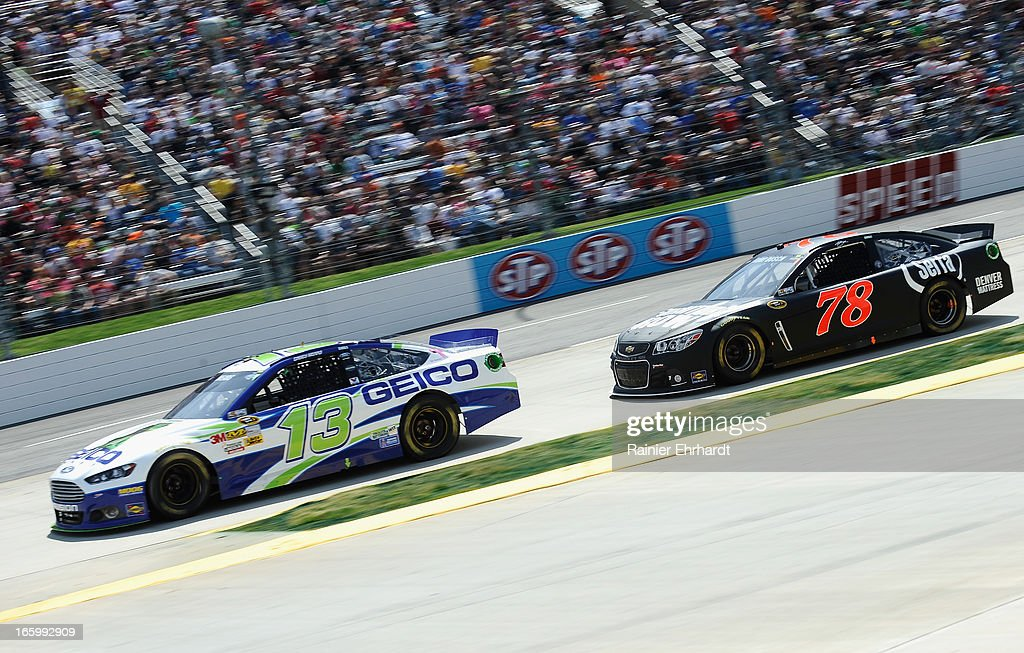 Casey Mears, driver of the #13 GEICO Ford, leads Kurt Busch, driver of the #78 Furniture Row/Serta Chevrolet, during the NASCAR Sprint Cup Series STP Gas Booster 500 on April 7, 2013 at Martinsville Speedway in Ridgeway, Virginia.