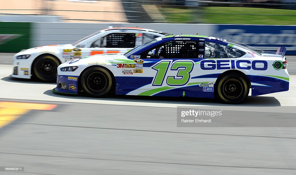 Casey Mears, driver of the #13 GEICO Ford, races Ken Schrader, driver of the #32 Federated Auto Parts Ford, during the NASCAR Sprint Cup Series STP Gas Booster 500 on April 7, 2013 at Martinsville Speedway in Ridgeway, Virginia.