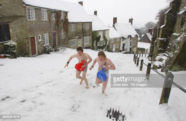 Casey Minns and James Jackson run back up after sledging down the iconic Gold Hill in Shaftesbury Dorset