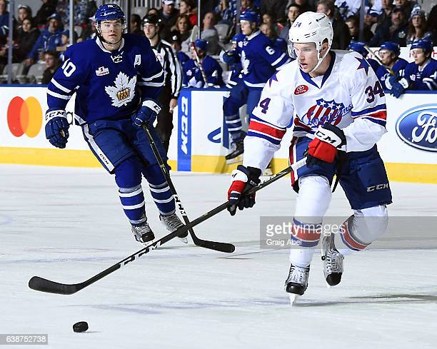 Casey Nelson of the Rochester Americans controls the puck past Byron Froese of the Toronto Marlies during AHL Game action on January 14 2017 at Ricoh...