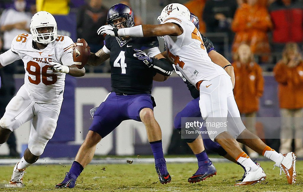 Casey Pachall #4 of the TCU Horned Frogs is sacked by Jackson Jeffcoat #44 of the Texas Longhorns as Chris Whaley #96 of the Texas Longhorns assists in the third quarter at Amon G. Carter Stadium on October 26, 2013 in Fort Worth, Texas.