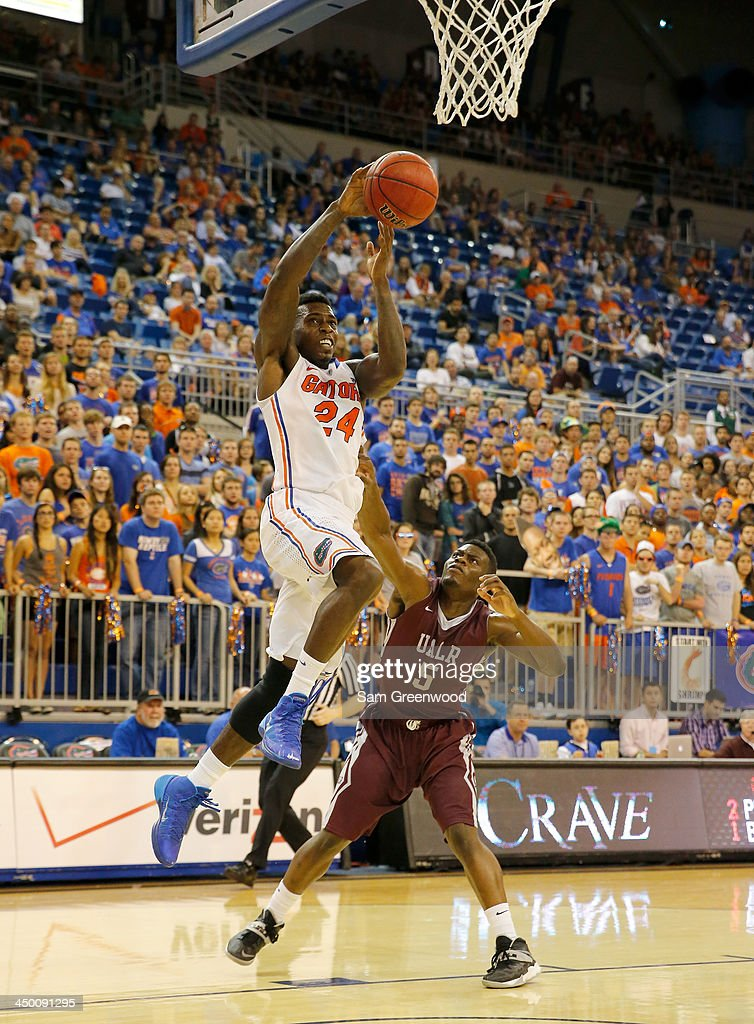 Casey Prather #24 of the Florida Gators attempts a shot over Kemy Osse #5 of the Arkansas Little Rock Trojans during the game at Stephen C. O'Connell Center on November 16, 2013 in Gainesville, Florida.
