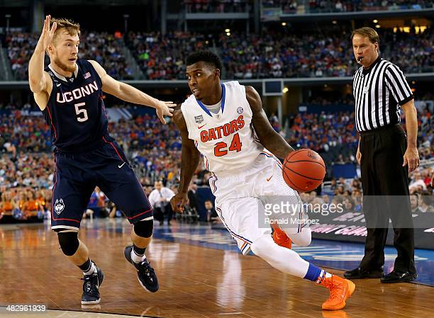 Casey Prather of the Florida Gators drives to the basket as Niels Giffey of the Connecticut Huskies defends during the NCAA Men's Final Four...