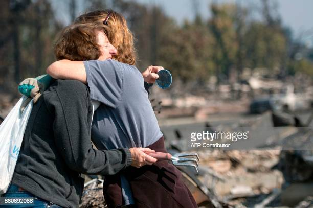 Casey Snow and Sue Tailorfellbaum hug after finding a memento at Tailorfellbaum's burned residence in Santa Rosa California on October 12 2017...