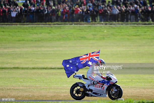 Casey Stoner of Australia and Ducati Marlboro Team celebrates with the flag of Australia the victory in MotoGP race at the end of MotoGP race of the...
