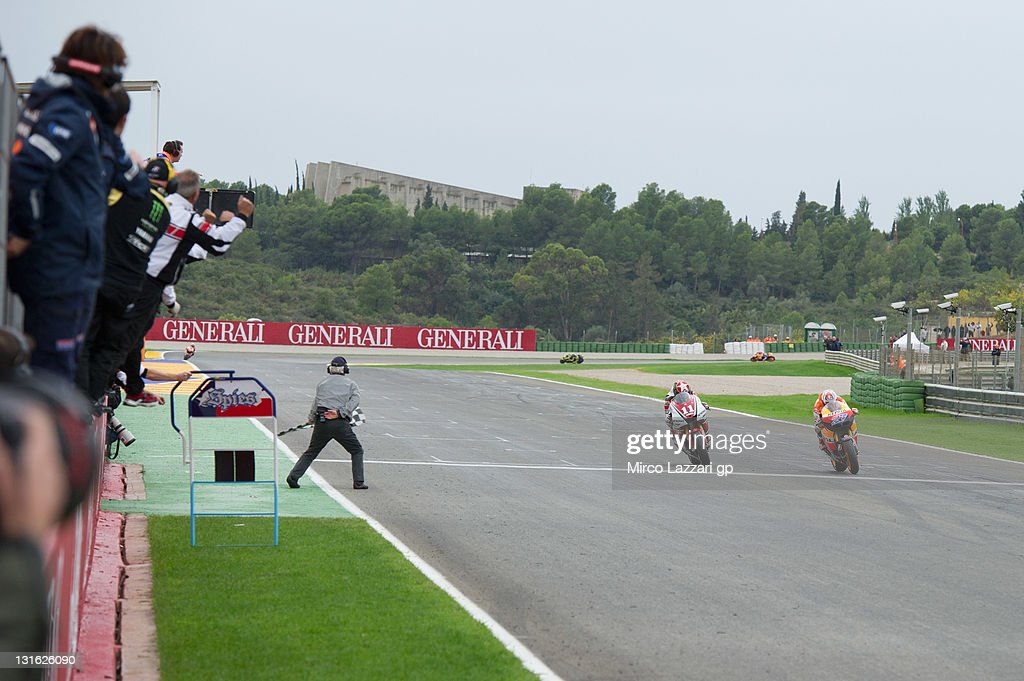Casey Stoner of Australia and Repsol Honda Team cuts the finish lane in front of Ben Spies of USA and Yamaha Factory Racing at the end of the MotoGP...