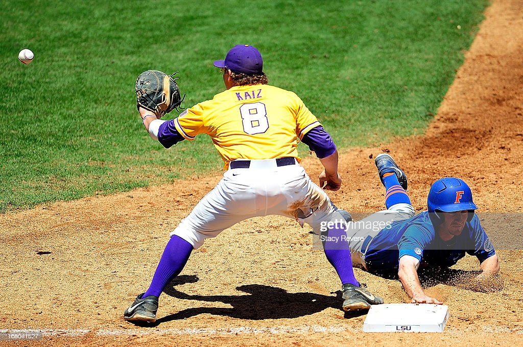 Casey Turgeon #2 of the Florida Gators dives into first base in front of a tag by Mason Katz #8 of the LSU Tigers during a game at ALex Box Stadium on May 4, 2013 in Baton Rouge, Louisiana.