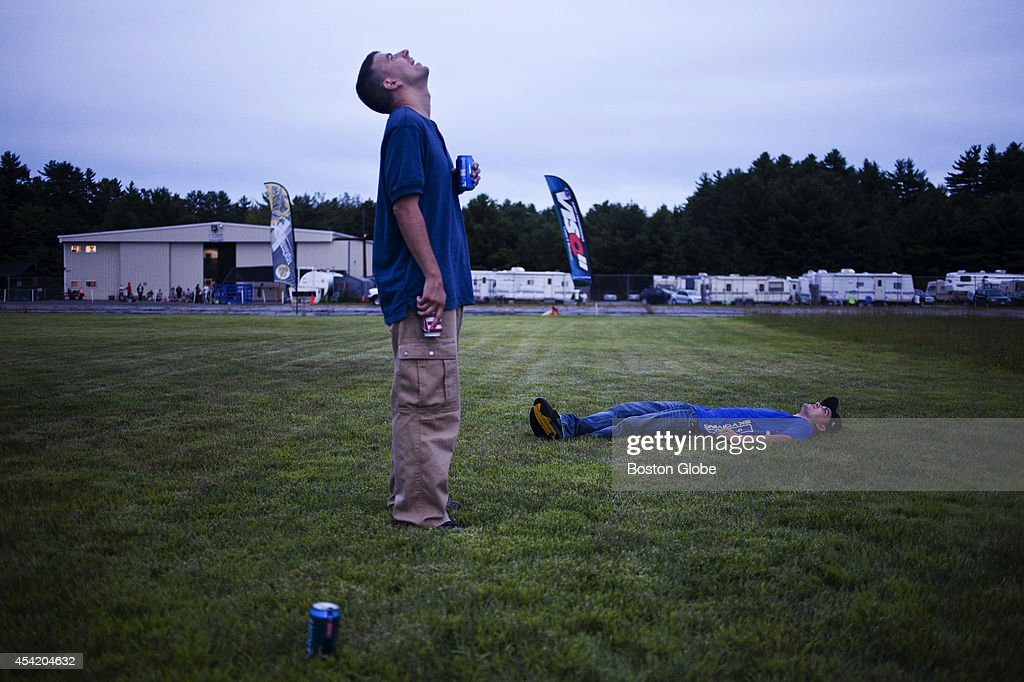 Casey Tylek, left, and Mitch Hamilton, right, drink beer while watching their fellow skydivers jump as they perform a 'swoop and chug' on August 16, 2014 at Jumptown in Orange, Mass.