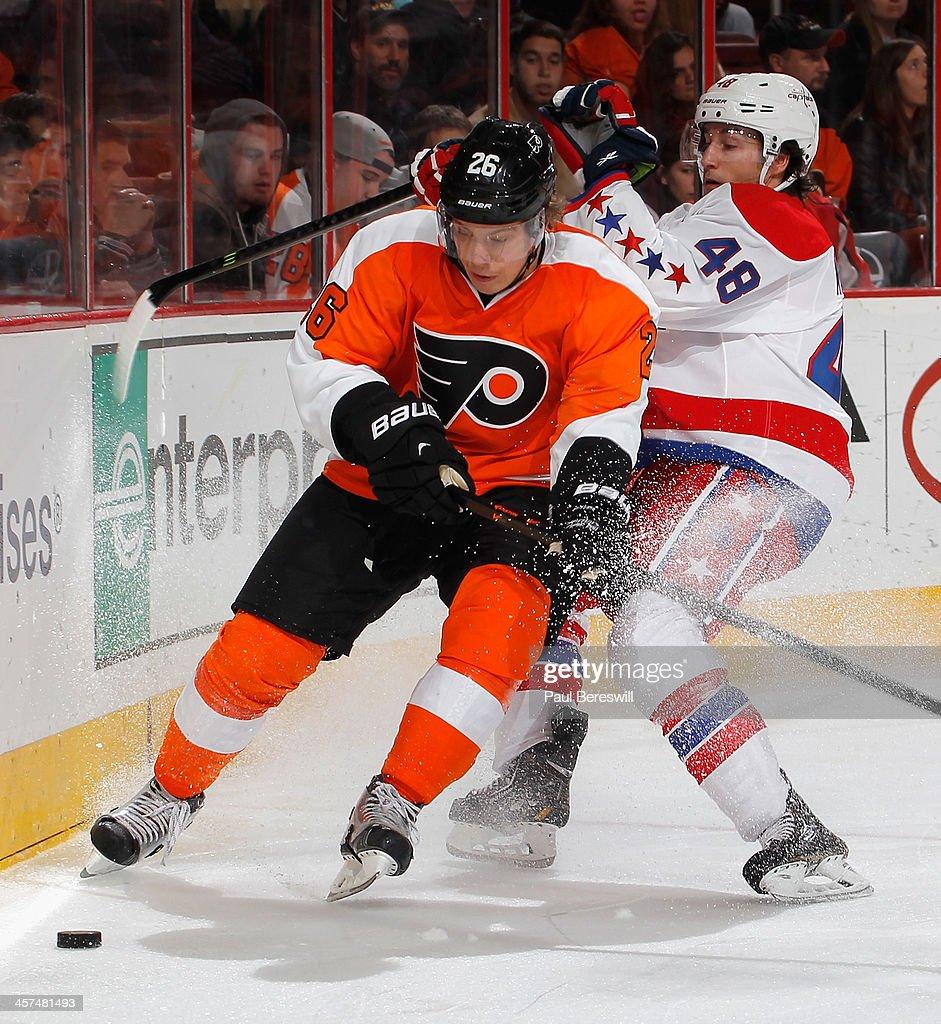 Casey Wellman #48 of the Washington Capitals checks Erik Gustafsson #26 of the Philadelphia Flyers during the third period of an NHL hockey game at Wells Fargo Center on December 17, 2013 in Philadelphia, Pennsylvania.
