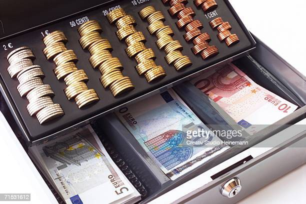 Cash box filled with coins and banknotes, elevated view, close-up