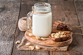 Cashew nut vegan milk non dairy in a glass lar with cashew nuts on wooden background