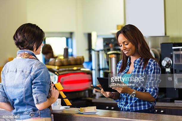 Cashier accepting credit card payment with digital tablet reader