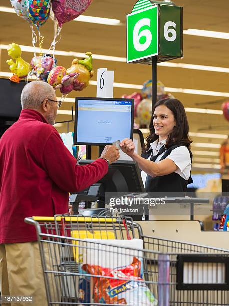 Cashier and customer at grocery store checkout