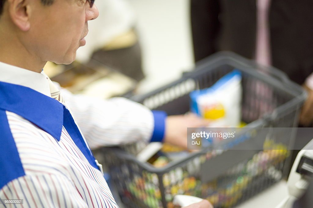 Cashier at cash register : Stock Photo