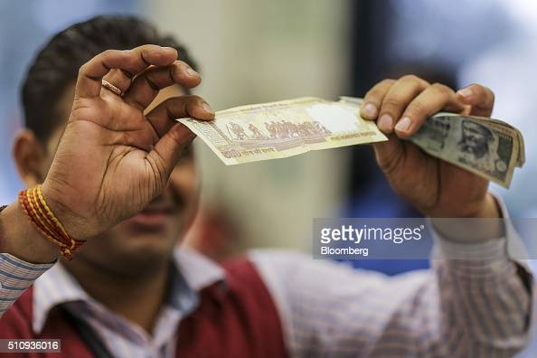 A cashier checks a five hundred Indian rupee banknote at a checkout counter of a DMart supermarket operated by Avenue Supermarts Ltd in Thane...
