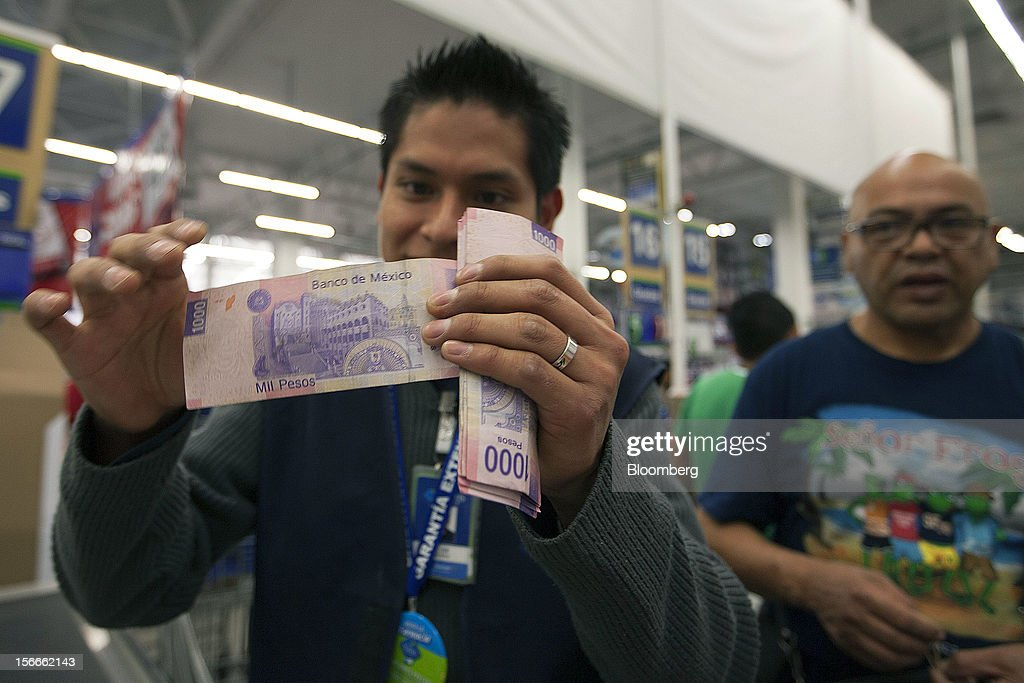 A cashier checks a thousand peso bill inside a Sam's Club store in Mexico City, Mexico on Saturday, Nov. 17, 2012. El Buen Fin, Mexico's equivalent of Black Friday, when the year's biggest discounts are offered by participating stores, is held on the third weekend of November and will run through Nov. 19. Photographer: Susana Gonzalez/Bloomberg via Getty Images