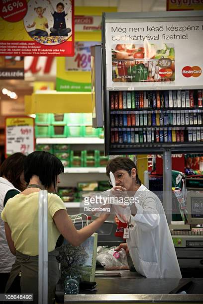 A cashier checks merchandise in a supermarket in central Budapest Hungary on Saturday Oct 16 2010 Hungary is taxing industry to meet budget deficit...
