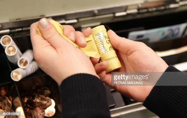A cashier counts euro coins before a shop opens in Vilnius on January 1 2015 AFP PHOTO / PETRAS MALUKAS