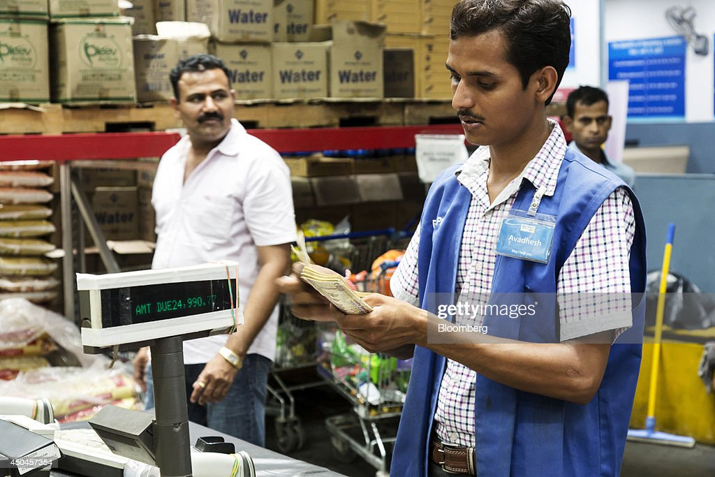 A cashier counts Indian rupee banknotes at a checkout counter inside a Walmart India Pvt. Best Price Modern Wholesale store in the town of Zirakpur on the outskirts of Chandigarh, Punjab, India, on Tuesday, June 10, 2014. India's consumer price index (CPI) figures and wholesale price inflation figures for May are scheduled for release on June 12 and 16 respectively. Photographer: Udit Kulshrestha/Bloomberg via Getty Images