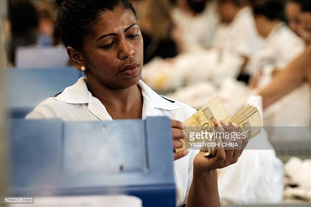 A cashier counts money at a checkout of a supermarket in Rio de Janeiro Brazil on December 21 as people shop for groceries for Christmas AFP PHOTO /...
